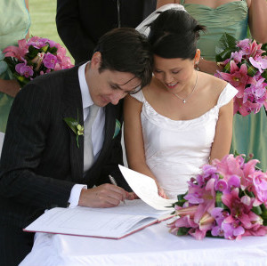 1280px-Bride_and_groom_signing_the_book